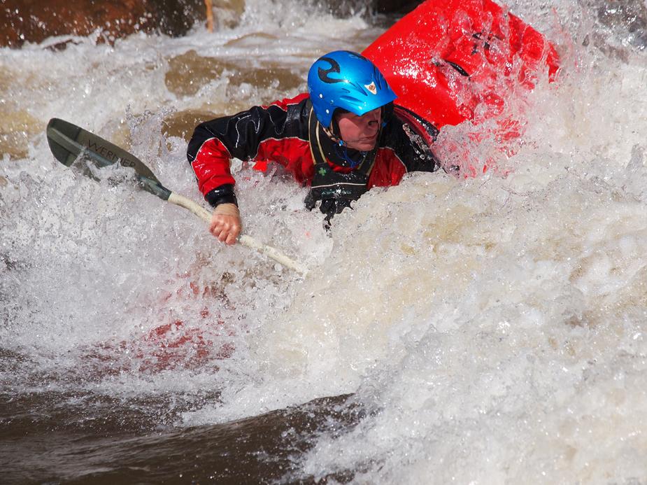 Man white water rafting in a red kayak