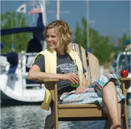 Woman in a deck chair on the dock while drinking a beer