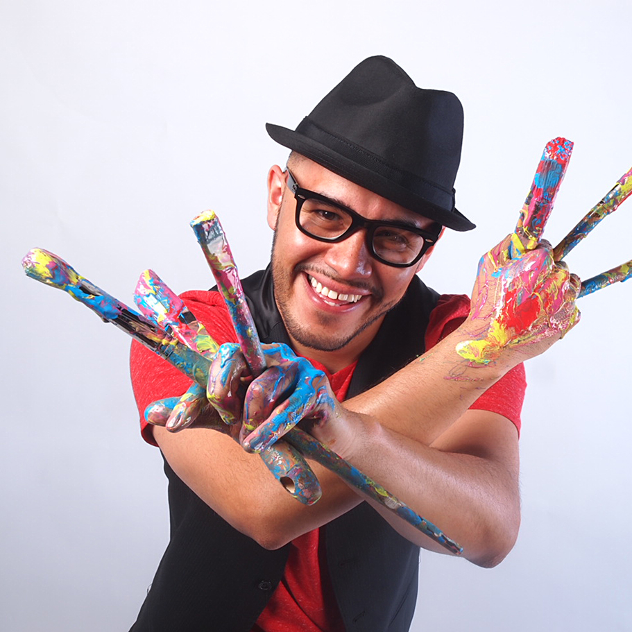 Artist with his hands and brushes covered in paint